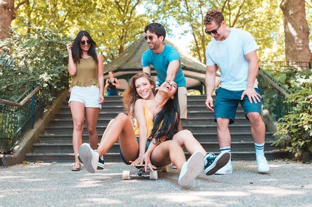 Gruppo di amici che si diverte con skateboard al parco