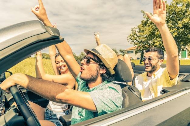 Gruppo di amici che si diverte in auto in giro per l'europa. amici in vacanza guidando sulla strada