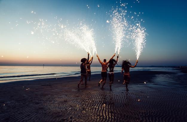 Gruppo di amici che si diverte in esecuzione sulla spiaggia con le stelle filanti