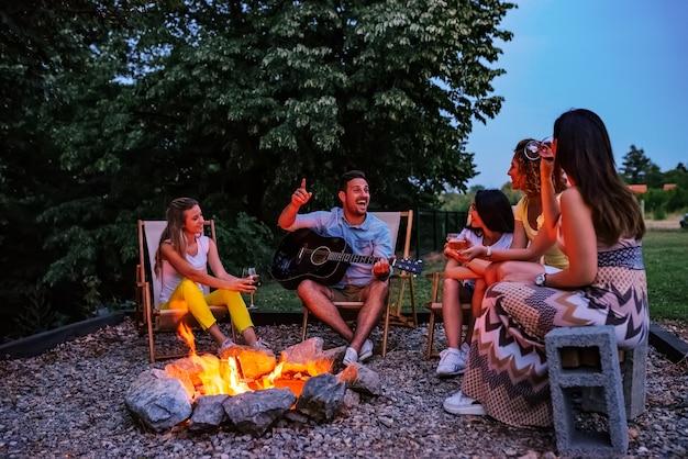 Gruppo di amici che si diverte intorno al fuoco. suonare la chitarra, cantare e bere.