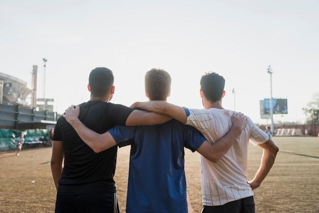 Gruppo di amici che stanno insieme di fronte allo stadio