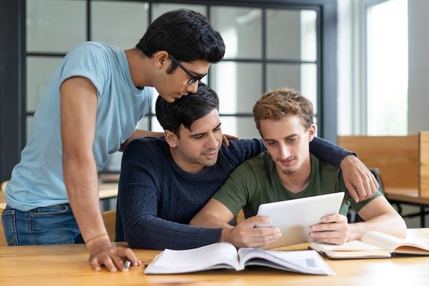 Gruppo di amici che studiano insieme, aiutandosi a vicenda