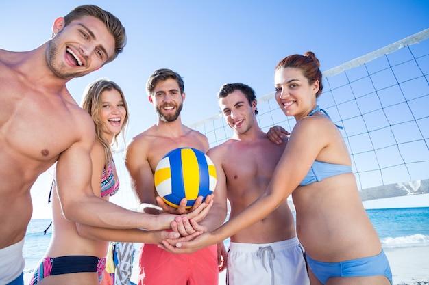 Gruppo di amici che tengono pallavolo e sorride alla macchina fotografica
