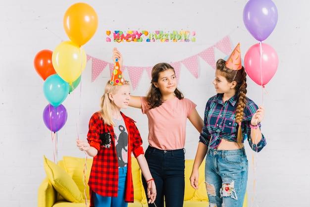 Gruppo di amici che tengono palloncini colorati durante il compleanno