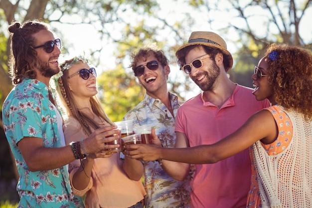 Gruppo di amici che tostano bicchieri di birra