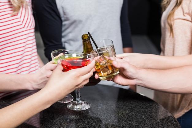 Gruppo di amici che tostano con birra e cocktail