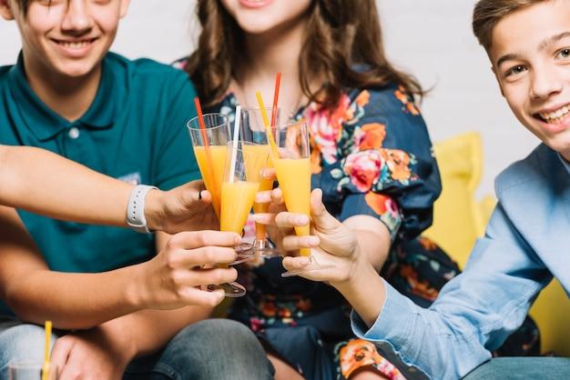 Gruppo di amici che tostano i bicchieri di succo di pilsner