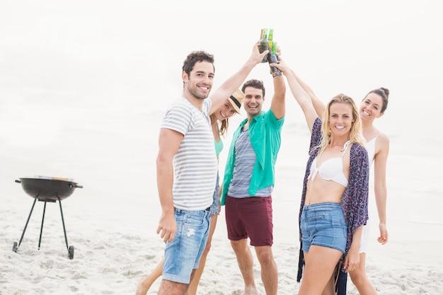 Gruppo di amici che tostano le bottiglie di birra sulla spiaggia