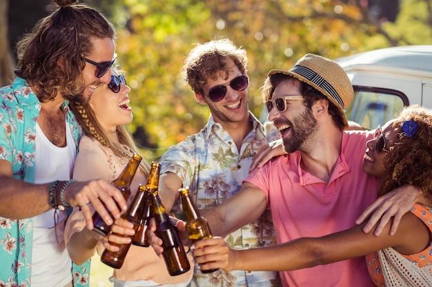 Gruppo di amici che tostano le bottiglie di birra