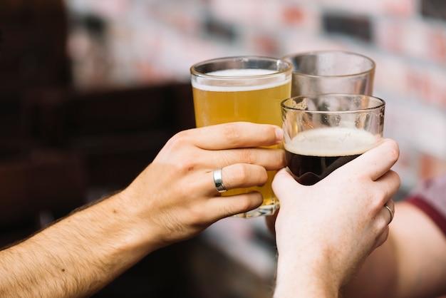 Gruppo di amici che tostano un bicchiere di bevande alcoliche