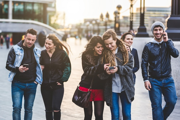 Gruppo di amici con i telefoni cellulari a londra