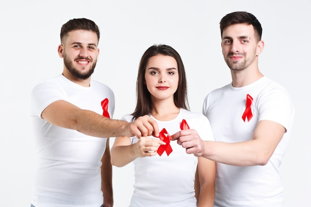 Gruppo di amici con l'acquerello del nastro rosso concetto di giornata mondiale contro l'aids. sullo sfondo bianco