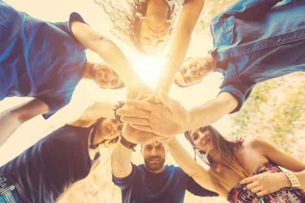 Gruppo di amici con le mani sulla pila e guardando verso il basso