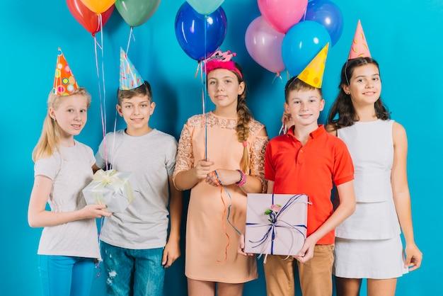 Gruppo di amici con regali e palloncini colorati su sfondo blu