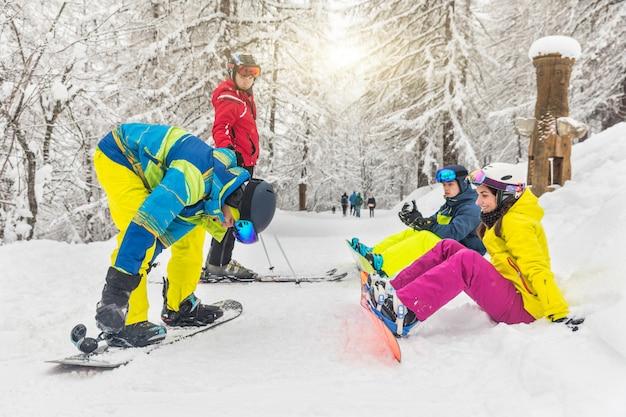 Gruppo di amici con sci e snowboard sulla neve