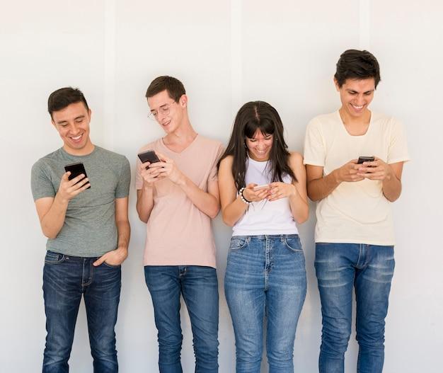 Gruppo di amici con telefoni cellulari