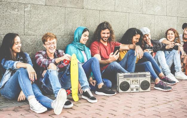 Gruppo di amici dei millennial che utilizzano smartphone e ascoltano musica all'aperto