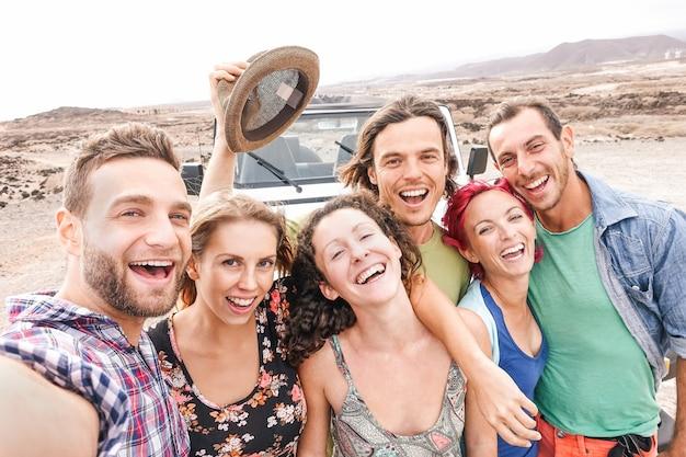 Gruppo di amici di viaggio che prendono selfie nel deserto durante un roadtrip