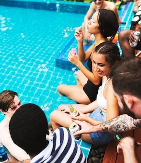 Gruppo di amici diversi che godono l'ora estiva a bordo piscina