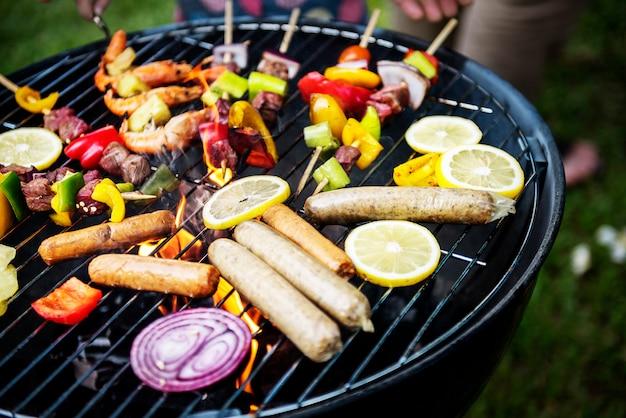 Gruppo di amici diversi grigliare all'aperto barbecue