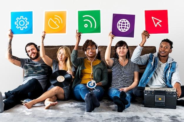 Gruppo di amici diversi tenendo icone della tecnologia