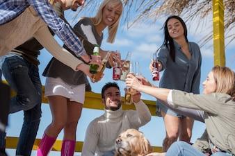 Gruppo di amici divertendosi in giornata d'autunno in spiaggia