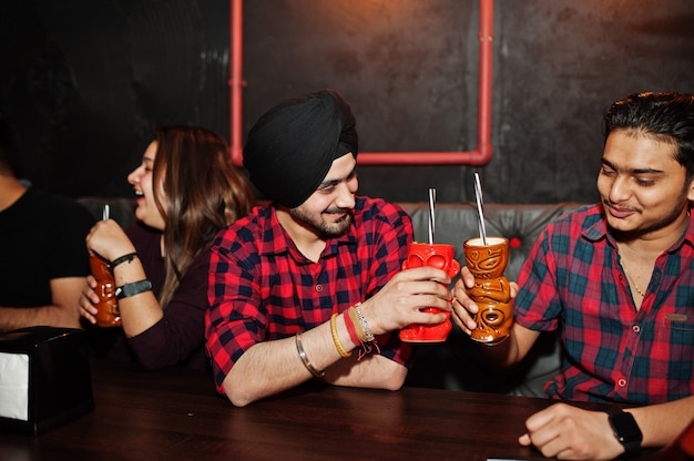 Gruppo di amici, divertirsi e riposare in discoteca, bere cocktail