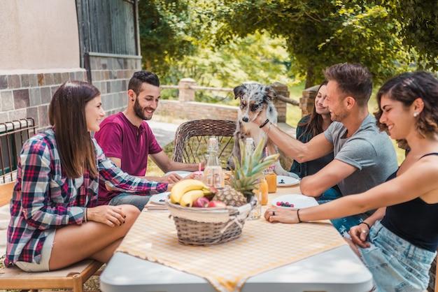 Gruppo di amici facendo colazione in una fattoria
