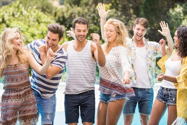 Gruppo di amici felici che ballano vicino allo stagno