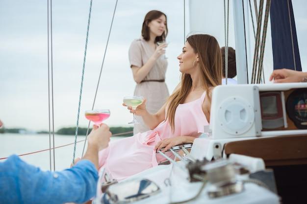 Gruppo di amici felici che bevono cocktail di vodka in una festa in barca all'aperto, allegro e felice