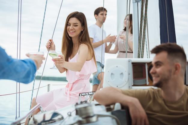 Gruppo di amici felici che bevono i cocktail della vodka in una barca