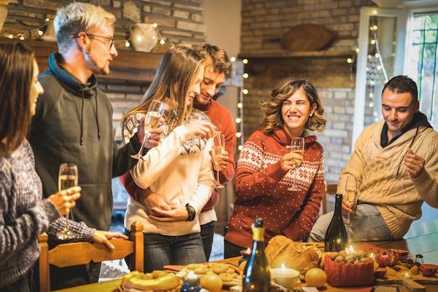 Gruppo di amici felici che celebra la festa di natale con vino bianco e cibo dolce a cena