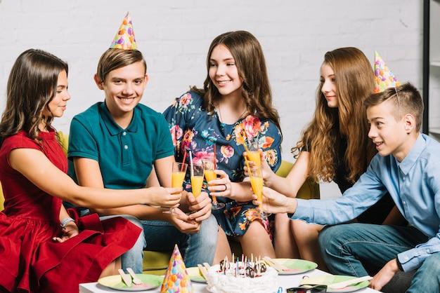 Gruppo di amici felici che esaminano il ragazzo di compleanno che tiene i vetri di succo nella festa