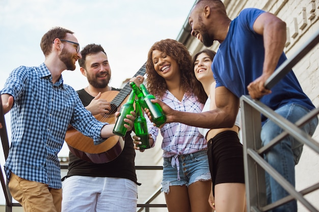 Gruppo di amici felici che hanno festa della birra nel giorno di estate. riposare insieme all'aperto, festeggiare e rilassarsi, ridere. stile di vita estivo, concetto di amicizia.