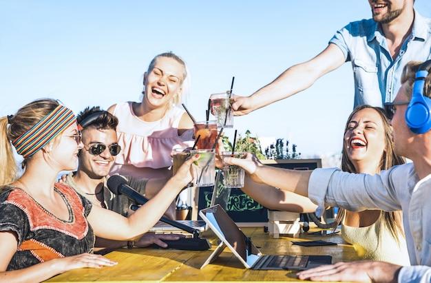 Gruppo di amici felici che tostano le bevande di moda al video streaming in diretta alla festa in spiaggia