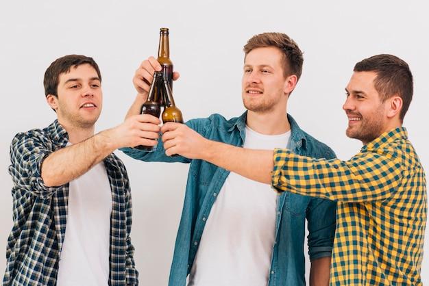 Gruppo di amici felici che tostano le bottiglie di birra contro fondo bianco