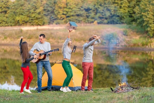 Gruppo di amici felici con la chitarra, divertirsi all'aperto, ballare e saltare vicino al lago nel parco il bellissimo cielo. divertimento in campeggio