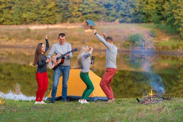 Gruppo di amici felici con la chitarra, divertirsi all'aperto, ballare e saltare vicino al lago sullo sfondo del parco il bel cielo. divertimento in campeggio