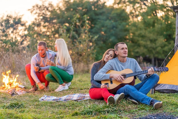 Gruppo di amici felici con la chitarra, divertirsi all'aperto, vicino al falò e tenda turistica. divertimento in campeggio famiglia felice