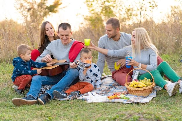 Gruppo di amici felici con tenda e bevande a suonare la chitarra in campeggio