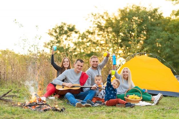 Gruppo di amici felici con tenda e bevande