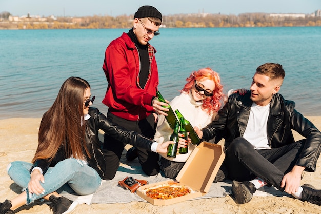 Gruppo di amici felici divertendosi e tintinnio bottiglie sulla spiaggia