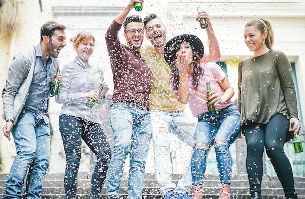 Gruppo di amici felici facendo festa bevendo birra e lanciando coriandoli