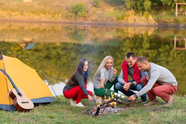 Gruppo di amici felici friggere salsicce sul fuoco vicino al lago.