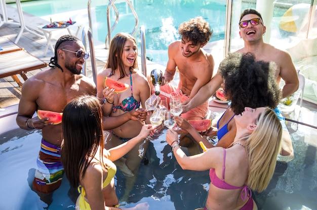 Gruppo di amici felici multirazziali facendo una festa in piscina giovani che ridono e si divertono bevendo champagne durante le vacanze di lusso