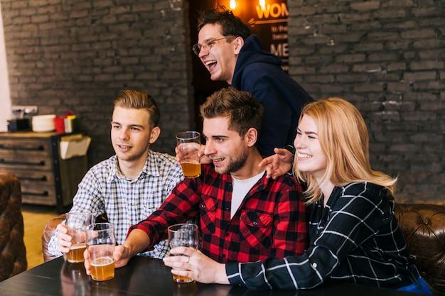 Gruppo di amici felici seduti insieme godendo la birra nel ristorante