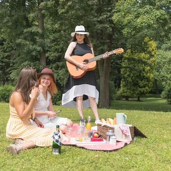 Gruppo di amici femminili che godono di musica e cibo nel picnic