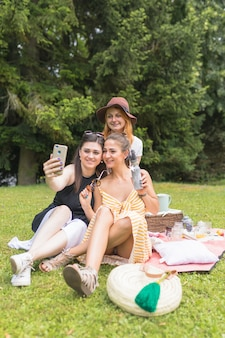 Gruppo di amici femminili prendendo selfie sul cellulare godendo nel picnic