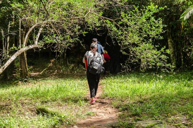 Gruppo di amici fotografo a piedi nella foresta con zaino fotocamera e treppiede.