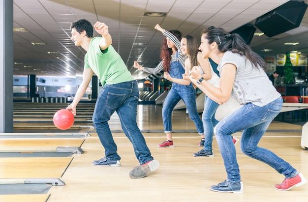 Gruppo di amici, giocare a bowling e divertirsi